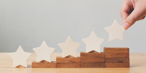 Hand putting wooden five star shape on table. The best excellent business services rating customer experience concept